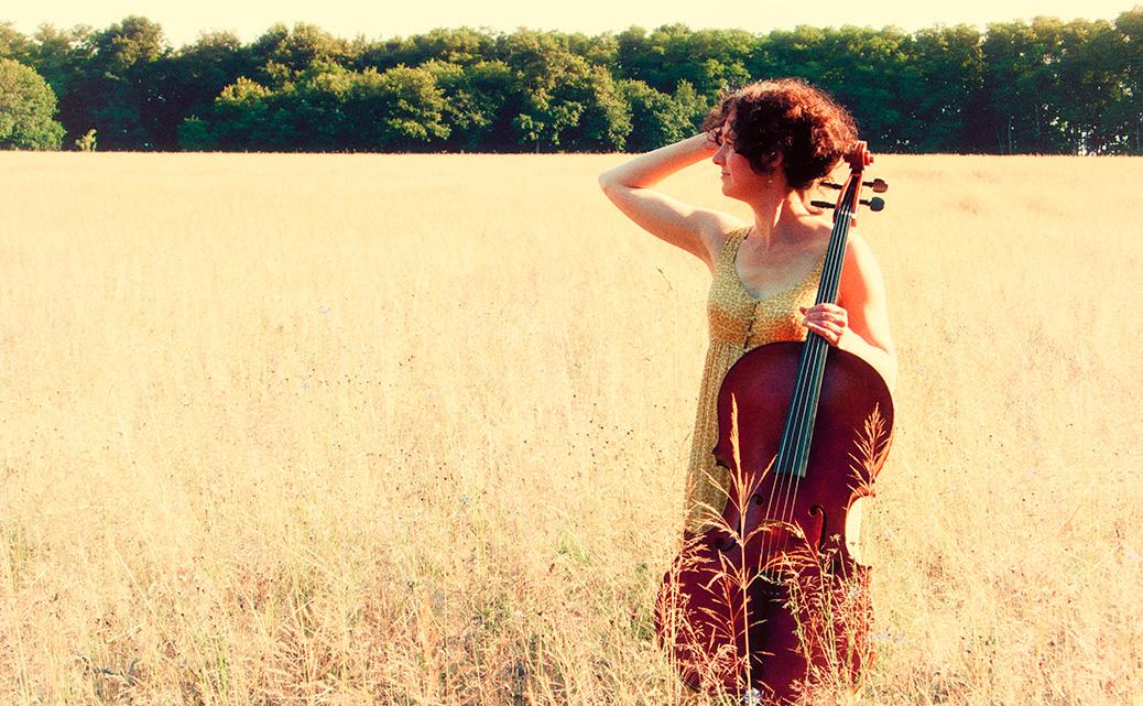 Celliste Mirjam Daalmans met cello in een korenveld